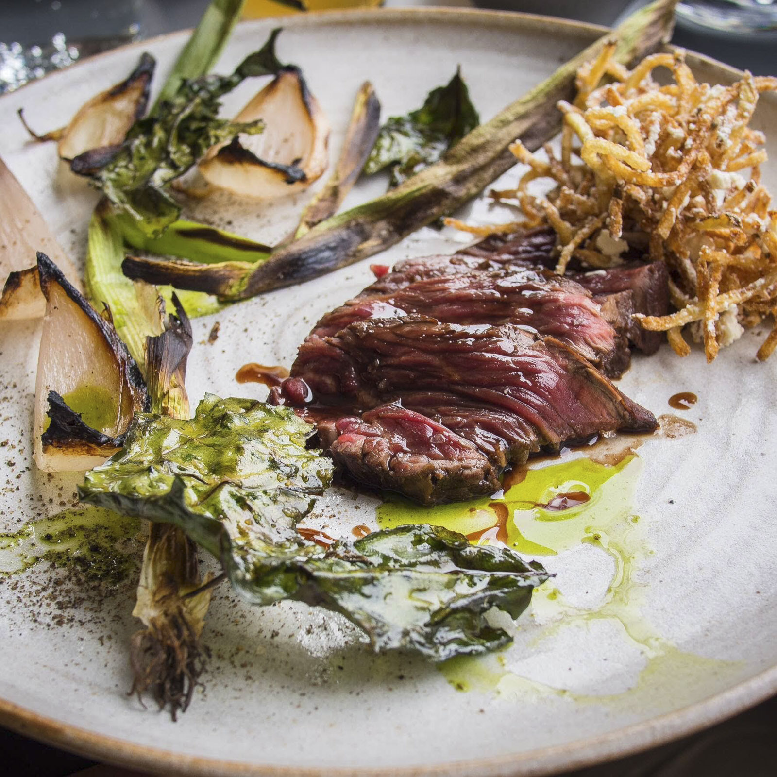 Steak onglet, salmuera, charred onion, and chicken fat curly fries, at Pidgin